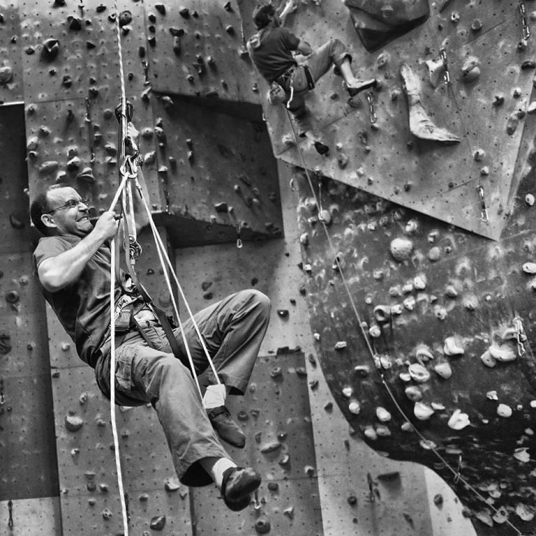 Homme en difficulté sur un mur d'escalade
