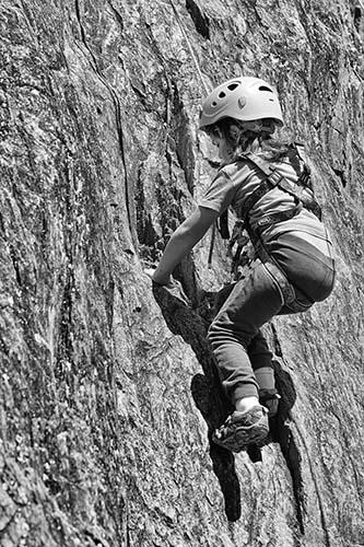 Petite fille escaladant une paroi rocheuse